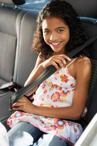 Young Girl Putting on Her Seat Belt in the Car